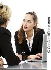 dos mujeres, durante, un, reunión negocio, con, computador portatil, blanco, plano de fondo, estudio