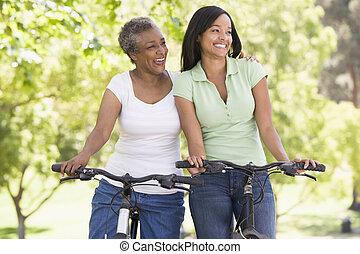 dos mujeres, en, bicicletas, aire libre, sonriente