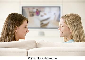 dos mujeres, en, sala, televisión que mira, sonriente