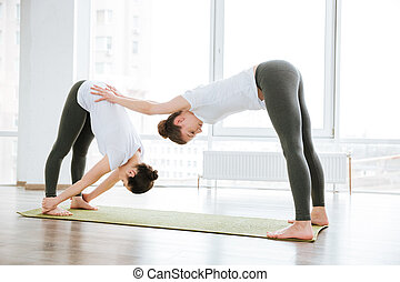 dos mujeres, extensión, piernas, en, yoga, centro