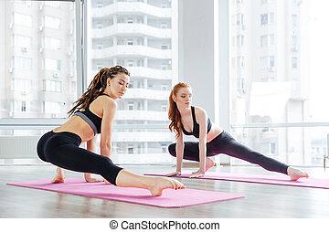 dos mujeres, extensión, piernas, juntos, en, estudio del yoga