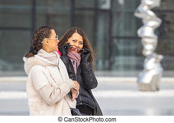 dos, mujeres hermosas, en, urbano, plano de fondo