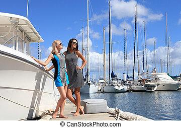 dos, mujeres hermosas, en, yate, puerto, plano de fondo