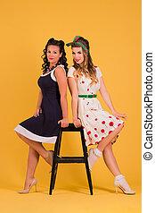 dos, mujeres jóvenes, en, vestidos, postura, en, amarillo, estudio, cerca, taburete