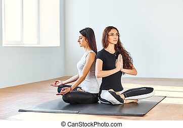 dos, mujeres jóvenes, practicar, yoga, en, posición lotus