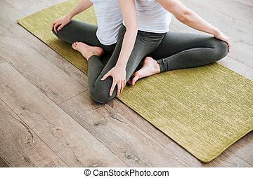 dos, mujeres jóvenes, practicar, yoga, en, verde, estera, en, estudio
