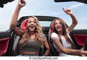dos, mujeres jóvenes, sentado, en el frente, asiento, de, un, convertible