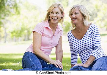 dos mujeres, sentado, aire libre, sonriente