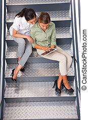 dos mujeres, sentado, escalera, utilizar, tableta de digital