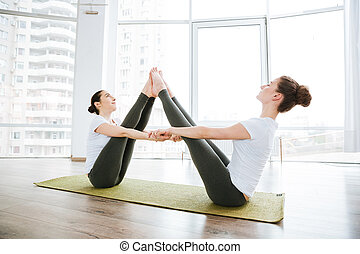 dos mujeres, sentado, y, extensión, piernas, en, estudio del yoga
