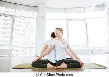dos mujeres, sentado, y, practicar, yoga, en, estudio, juntos