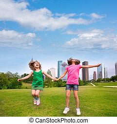 dos niñas, amigos, saltar, feliz, llevar a cabo la mano, en, perfil de ciudad