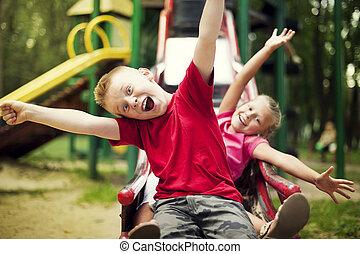 dos, niños, diapositiva, en, patio de recreo