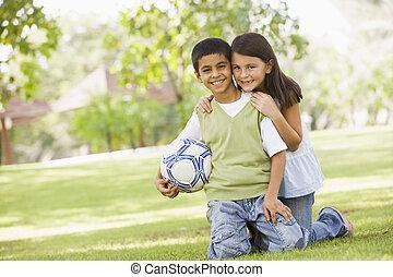 dos niños, jugar al balompié, en el estacionamiento