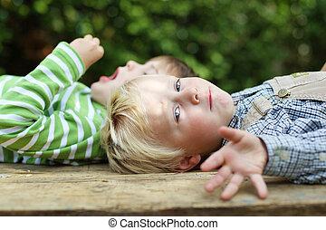 dos niños, relajante, en el jardín