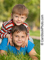 dos, sonriente, hermanos, en la hierba