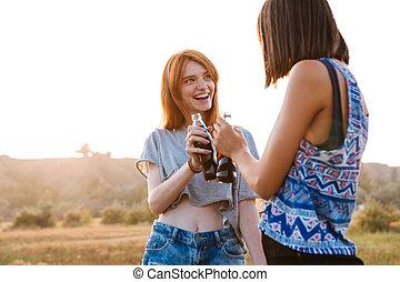 dos, sonriente, mujeres jóvenes, bebida, soda, aire libre