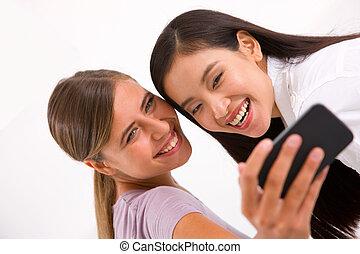 dos, sonriente, mujeres jóvenes, toma, autorretrato, con, teléfono celular