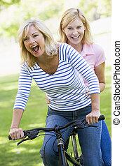 dos, uno, bicicleta, aire libre, sonriente, amigos
