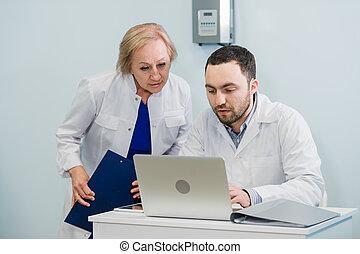 dottore infermiera, riesaminazione, informazioni pazienti, su, uno, computer portatile, in, un, ufficio, regolazione