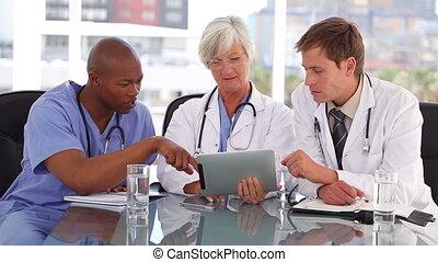dottore maturo, usando, uno, touchscreen, con, lei, colleghi