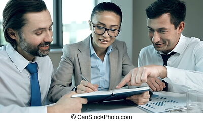 Double Agent - Close up of two managers dictating tasks to a...