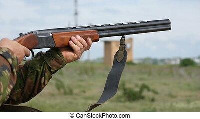 Double barrel shotgun in profile shoots outdoors in autumn in slow motiom
