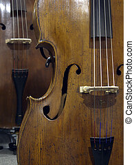 View of double-bass, showing beautiful grained old wood, violin corners, f-holes, bridge and lower half of the fingerboard and strings.
