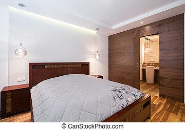 Double bed in wooden bedroom