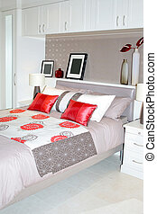 Modern bedroom with double bed and red pillows