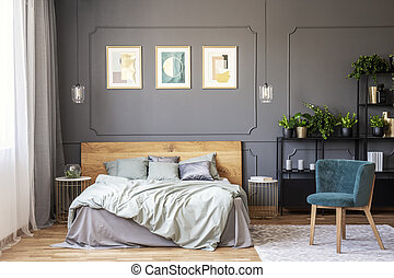 Double bed with grey bedding and wooden headboard standing...