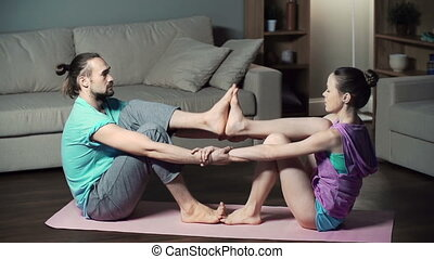 Double Boat - Couple practicing in-home yoga performing...