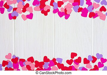 Double border of colorful Valentines Day paper hearts against a white wood background
