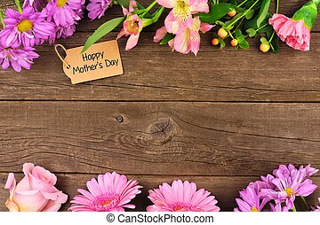 Double border of flowers with Mothers Day gift and tag against rustic wood