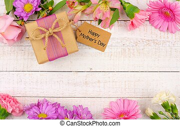 Double border of flowers with Mothers Day gift and tag against white wood