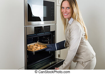 Double burden: business woman baking cookies in the kitchen