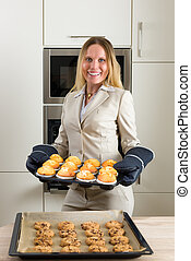 Double burden: business woman baking cupcakes in the kitchen