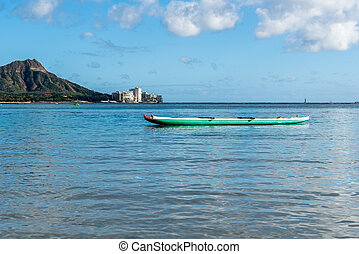 Double canoe in the water on Waikiki Beach in Honolulu, Hawaii with Diamond Head in the background