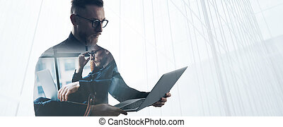 Double exposure bearded businessman wearing black shirt and glasses,holding contemporary notebook hands. Portrait young banker using laptop in modern office, skyscraper background. Wide