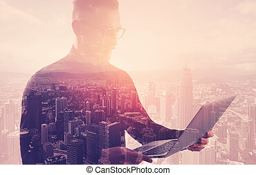 Double exposure businessman wearing black shirt and glasses.Banker holding contemporary notebook hands.Using work online banking system. Modern city sunset background. Horizontal mockup
