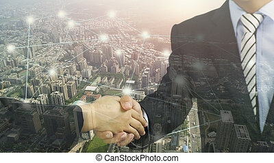 double exposure city and shaking hand, concept in connection and success in bussiness