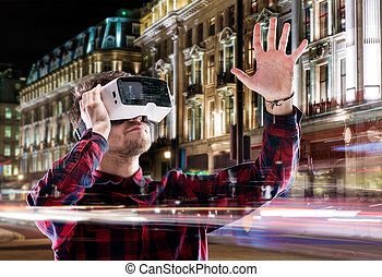 Double exposure, man wearing virtual reality goggles, night ...
