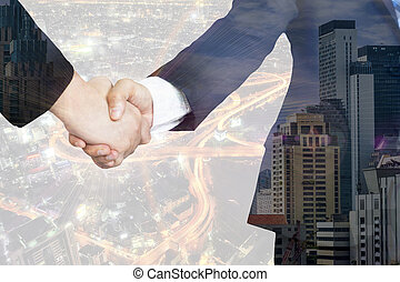 Double exposure of business handshake and city