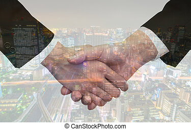 Double exposure of Business handshake over cityscape