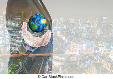 Double exposure of Business man holding the small world in his hands with cityscape (Elements of this image furnished by NASA)
