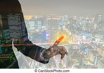Double exposure of business man touching an imaginary screen...