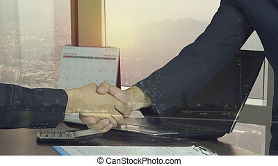 double exposure of businessman shaking hand and night city