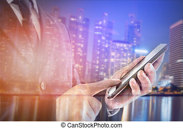 Double exposure of city and businessman standing touch the screen on smartphone.