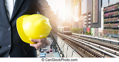Double exposure of engineer holding helmet on on Sky train and high buildings in the city background.