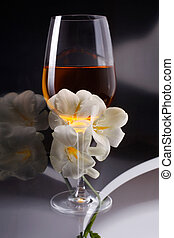 Double exposure of glass of wine over white freesia, a vertical